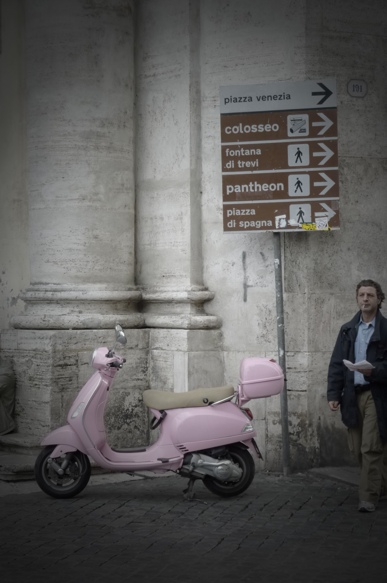 A Roman walks past a pink motorino in Rome